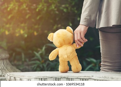 boy hold teddy bear in park.autism concept