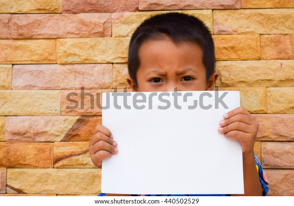 boy hold white blank paper with stone wall background