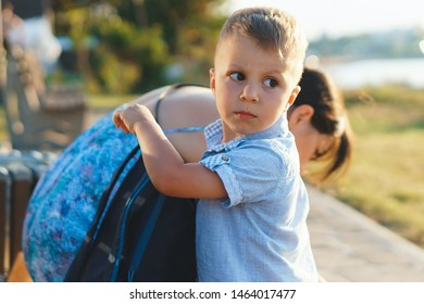 boy holding backpack on bench with mother