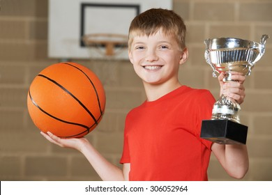 Boy Holding Basketball And Trophy In School Gymnasium
