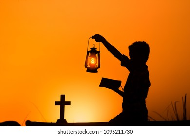 Boy holding bible and praying to god with oil lamp, christian concept