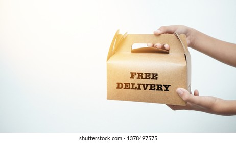 "Boy holding brown box with "" free delivery "" label."