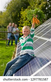 Boy holding bunch of carrots near solar panels with family smiling at camera