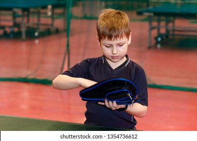 the boy is holding a cover for a racket for table tennis indoors