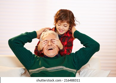 Boy holding the eyes closed of his happy grandfather