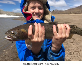 Boy holding fish he caught fly fishing in a lake in late winter