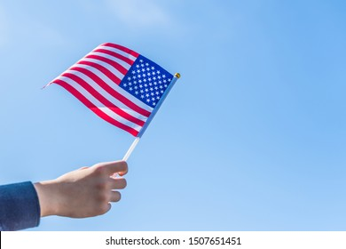 Boy holding Flag of America on the blue sky backgrouns. USA.Concept