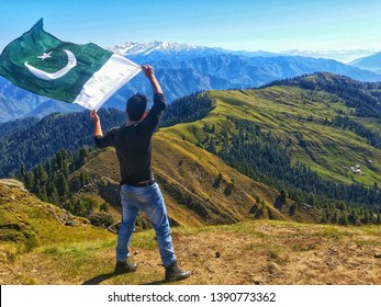 a boy holding the flag of pakistan on ganga choti top infront of indian mountains