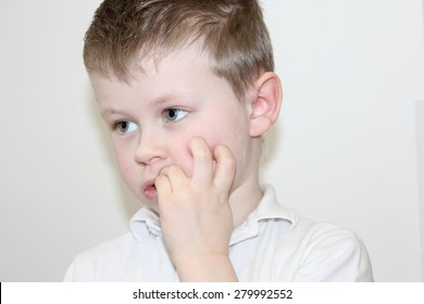 A boy holding his fingers in his mouth. A child on a white background. The child is in focus, face and hands closeup. His face has a thoughtful look. The baby's eyes look toward.