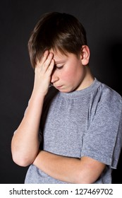 boy holding his head on a black background