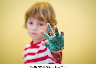 Boy holding up his paint covered hand to the camera