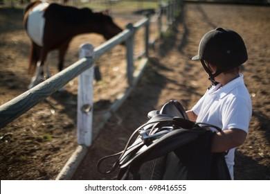 Boy holding horse saddle on a sunny day