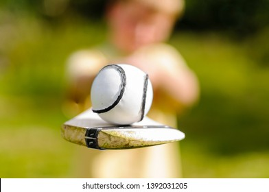 Boy holding up a hurling bat and sloitar (ball) used in the Irish game of Hurling.