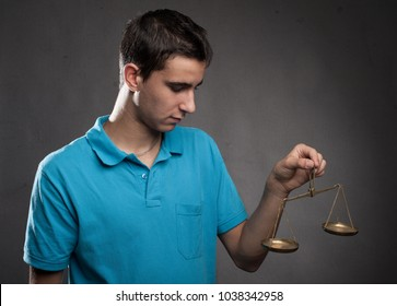 boy holding a justice scale on a gray background