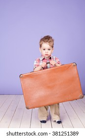 A boy holding a large suitcase