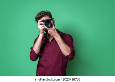 Boy holding a mirrorless camera and taking a picture while looking through the electronic viewfinder.