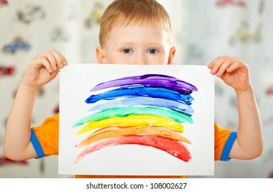 boy holding paper with painted  rainbow