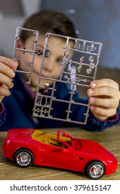 boy holding parts of a model car, shallow depth of field