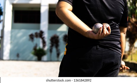 A boy holding petanque ball or boules in hand behind his back ready to start the game.
