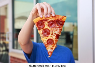 Boy holding a piece of pepperoni pizza in front of his face