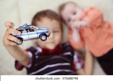 Boy holding a police car near baby brother