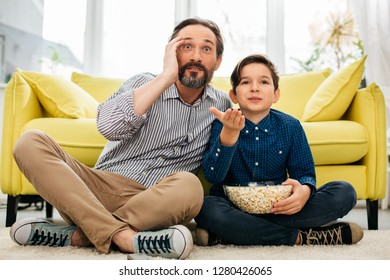 Boy holding popcorn and his father looking impressed while sitting on the floor and watching amazing game on TV