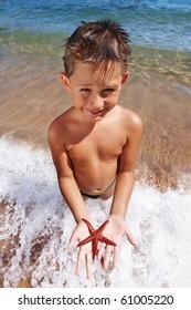 Boy holding a red starfish on sandy beach in Budva Montenegro