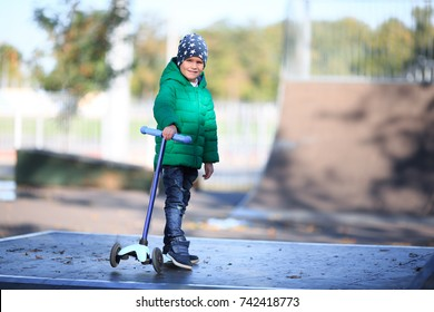 A boy is holding a scooter on the street.