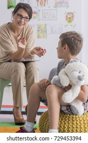 Boy is holding stuffed toy and is looking at pedagogue during therapeutic meeting in classroom