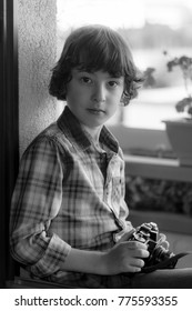The boy is holding a vintage camera. Portrait. Black and white.