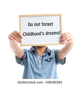 Boy holding whiteboard on white background with message do not forget childhood's dreams