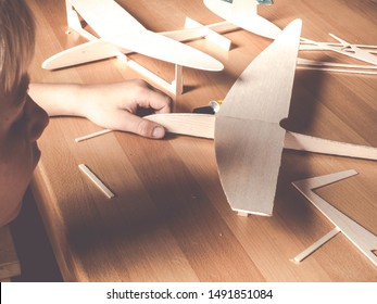 boy holding a wooden plane model; aircraft construction made of balsa wood