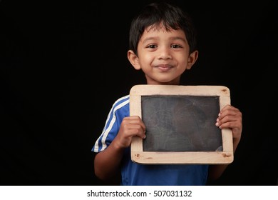 A boy holds a black slate in his hands