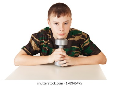 the boy holds a dumbbell in hand leaning on a table