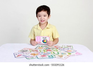 Boy holds flashcard with B - isolated white