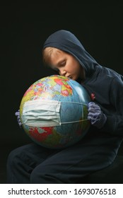 """Boy hold""""s globe with medical mask to save the planet"""