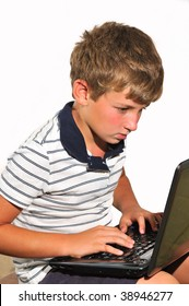 The boy holds a laptop on his knees and do homework
