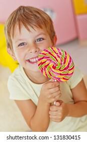 A boy holds a large colorful lollipop