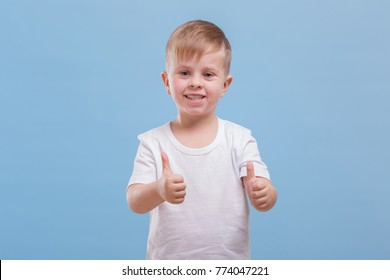 A boy holds two thumbs up against a blue background