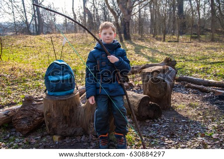 boy with homemade bow and arrows. sitting on a stump in the forest in a