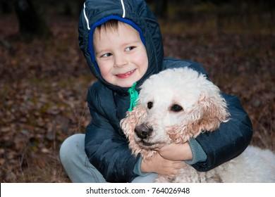 the boy is hugging a big poodle