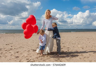 Boy hugging his mother on the beach. Young woman and two children relaxing on the sea shore with red heart balloons.