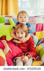 Boy hugs his sister's neck tightly while playing on the chair