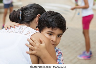 Boy hugs woman with pensive look on a playground while other kids play