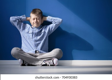 Boy with hypersensitive auditory is covering ears while siting on floor in empty room
