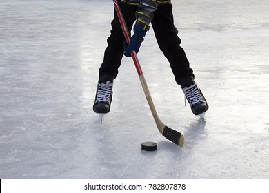A boy ice hockey amateur player  with a stick and a puck on ice. Feet in  hockey skates and a stick and a puck and ica background. Half of amateur hockey player's figure, ready to hit the puck on ice.