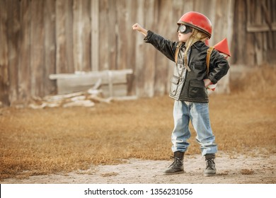 Boy in the image of a rocketman play in the backyard of the house