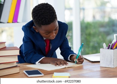Boy imitating as businessman writing on diary at desk in office