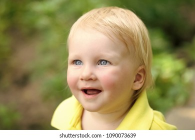 Boy infant smile with blue eyes on adorable face and blond hair on natural environment. Child, childhood, family. Happiness, innocence, infancy, future concept