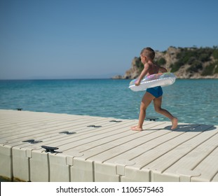 Boy with inflantable ring juping in ocean of wooden pier